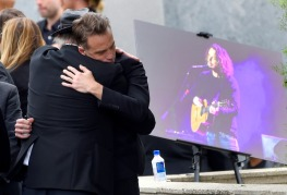 Matt Cameron, of Soundgarden, right, hugs a guest at a funeral for Chris Cornell, pictured right, at the Hollywood Forever Cemetery on Friday, May 26, 2017, in Los Angeles. (Photo by Chris Pizzello/Invision/AP)