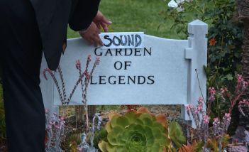 """Un uomoa aggiunge un foglio con la scritta """"Sound"""" al cartello che segnala la sezione Garden of Legends dello Hollywood Forever Cemetery , dove da ieri è sepolto il chitarrista dei Soundgarden Chris Cornell (FREDERIC J. BROWN/AFP/Getty Images)"""